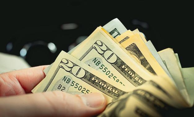 A man holding us dollar bills in his hand in dark environment