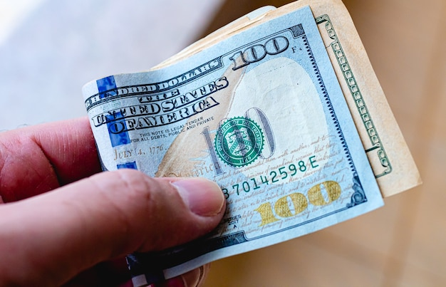 A man holding us dollar bills in his hand with the one hundred dollar bill highlighted