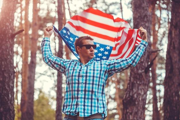 米国の旗を持った男。アメリカの独立記念日を祝う