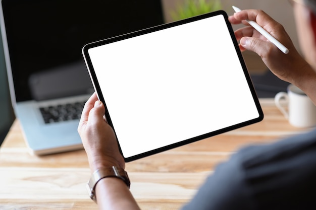 Man holding and using blank screen tablet