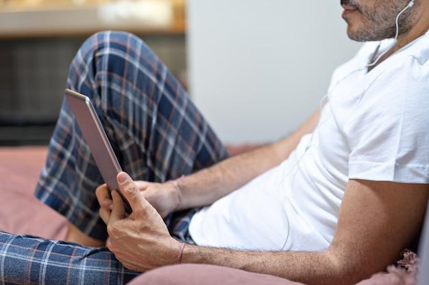 ピジャマと自宅のベッドでデジタルタブレットとヘッドフォンを使用して保持している男