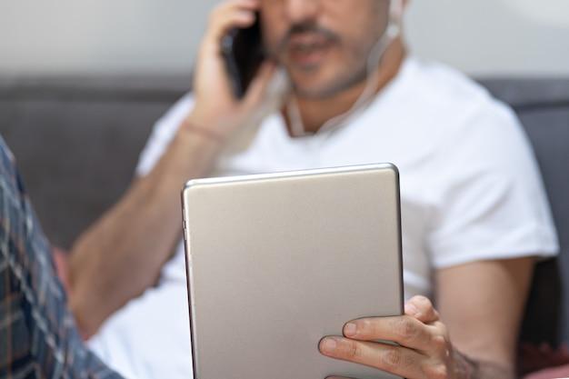 デジタルタブレットのスマートフォンのビデオ通話を使用して保持している男。
