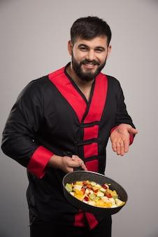 Мужчина держит овощи на темной сковороде.