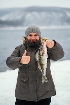 Uomo che tiene vittoriosamente un pesce che ha catturato