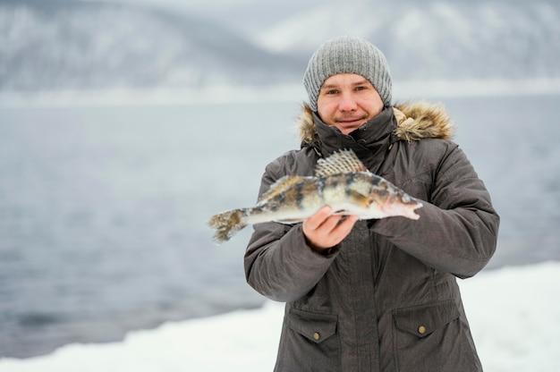 Мужчина победно держит рыбу, которую он поймал