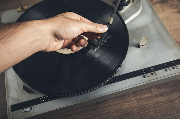 Man holding vintage record player on table