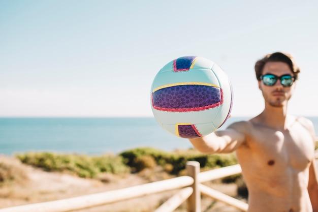 Мужчина держит волейбол на пляже