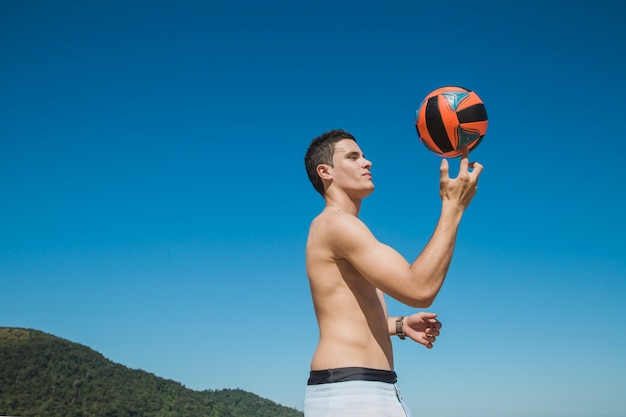 Man holding volleyball with fingers
