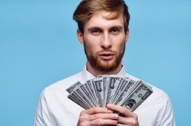 顔の富のクローズアップの近くにお金の札束を保持している男