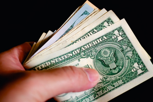 A man holding a wad of us dollar bills in closeup photo with black background