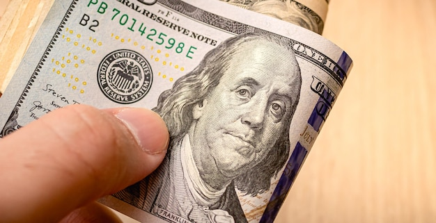 A man holding a wad of us dollar bills in closeup photo