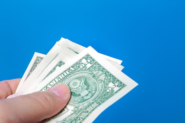 A man holding a wad us dollar bills with blue background