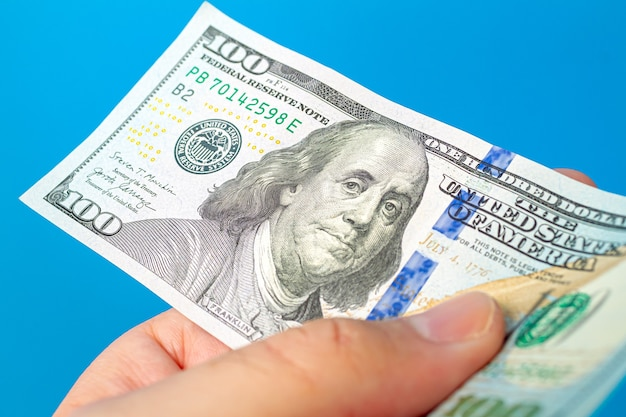 A man holding a wad us dollar bills with white background