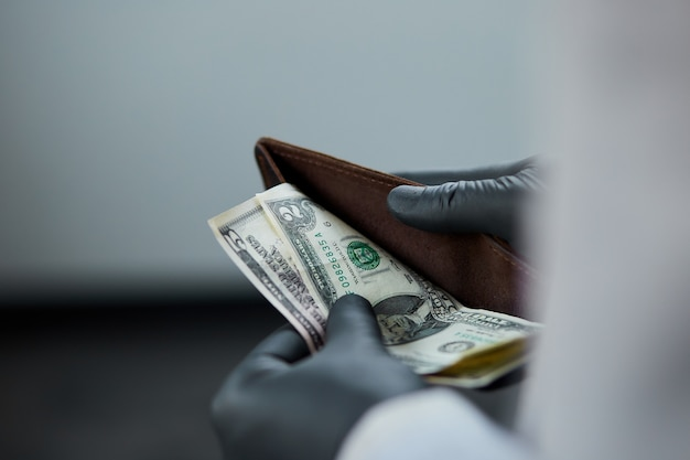 Man holding a wallet with  money dollars  in hand in black medical gloves. coronavirus crisis. save money. no maney.