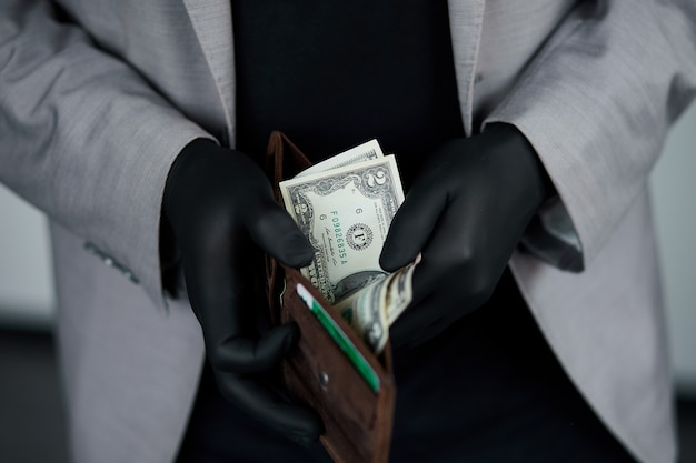 Man holding a wallet with  money dollars  in hand in black medical gloves. save money. no money.  the world crisis