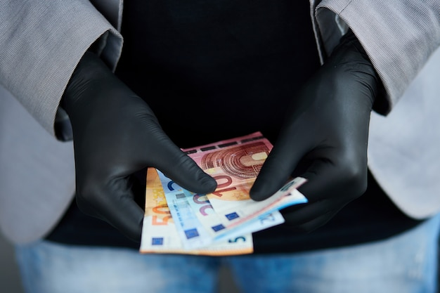 Man holding a wallet with  money euro in hand in black medical gloves. coronavirus crisis. save money. the world crisis