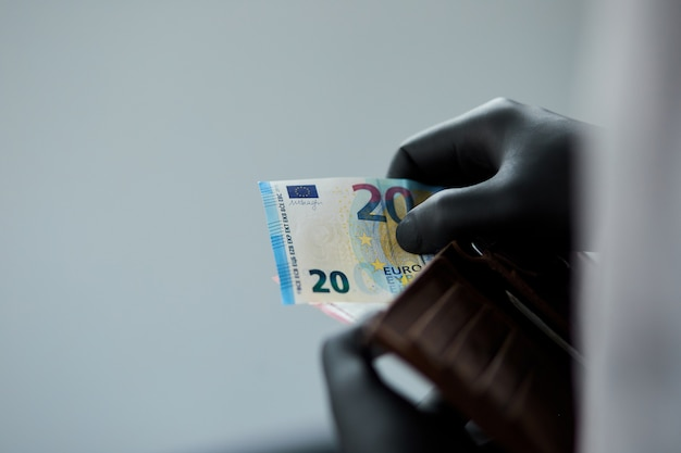 Man holding a wallet with money euro in hand in black medical gloves