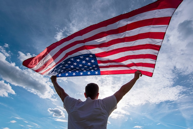 Man holding waving american usa flag in hands in usa, concept picture