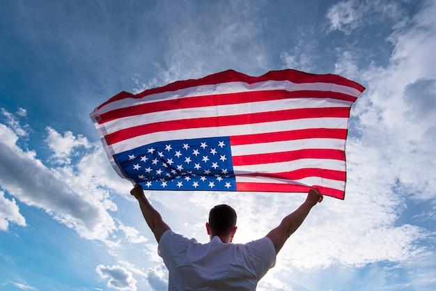 Мужчина держит в руках американский флаг сша, концепция изображения