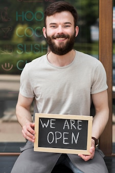 Man holding we are open sign