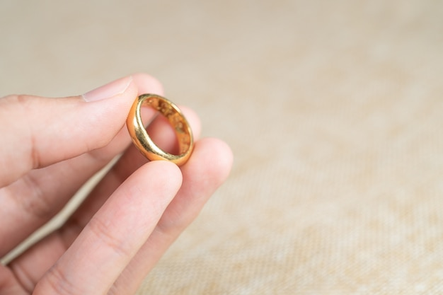Man holding wedding ring over brown sack background.