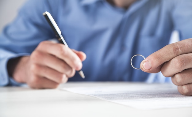 Man holding a wedding ring and signing divorce contract.