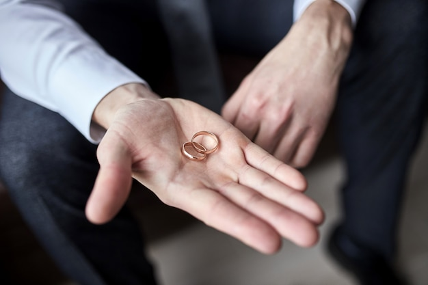 Man holding wedding rings, groom getting ready in the morning before ceremony