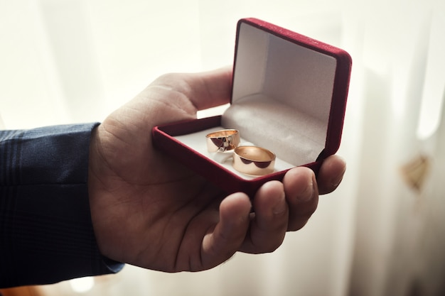 Man holding wedding rings lie in a beautiful  box, groom getting ready in the morning before ceremony