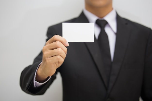 Man holding white business card on concrete wall background