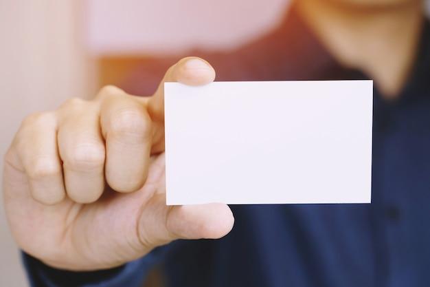 Мужчина держит белую визитку на фоне бетонной стены