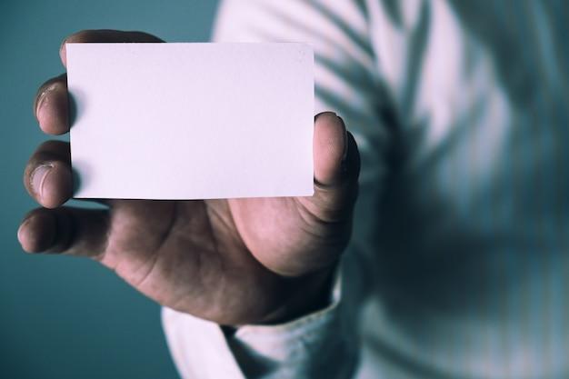 Человек с белой визитной карточкой на фоне бетонной стены