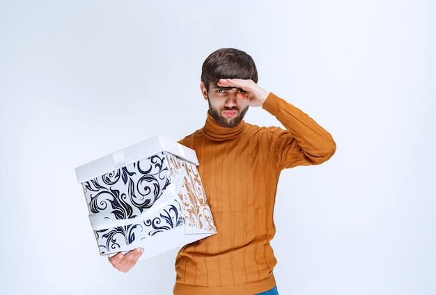 Uomo che tiene una scatola regalo bianca con motivi blu che emettono suoni per notare qualcuno.