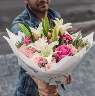 ピンクのバラと白いユリの花束を持って男