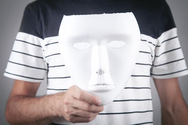 Man holding white mask. fake, anonymous