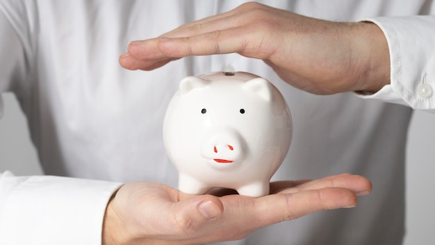 Man holding a white piggy bank