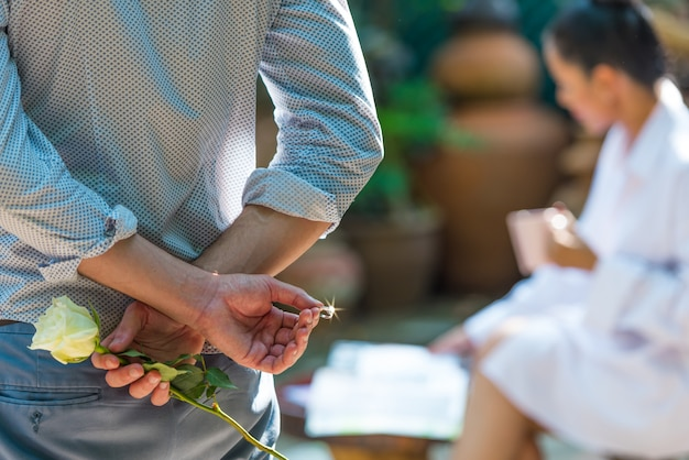 Man holding white rose and wedding ring behind his back for making marriage proposal.