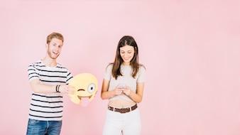 Man holding winking eye emoji near smiling woman using cellphone