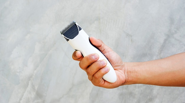 Man holding wireless hair clipper in his hand.
