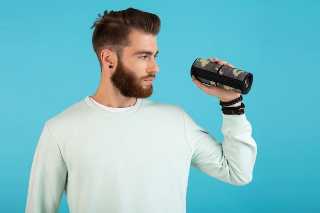 Uomo con altoparlante wireless che ascolta musica isolato su blue