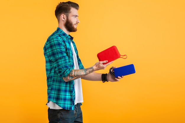 Uomo con altoparlante wireless che ascolta musica isolato su giallo