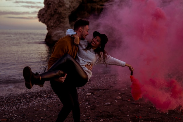 Man holding woman in arms with pink smoke bomb