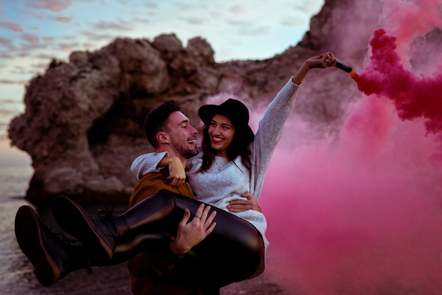 Man holding woman in arms with smoke bomb