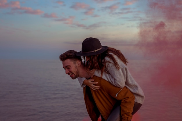 Man holding woman on back on sea shore