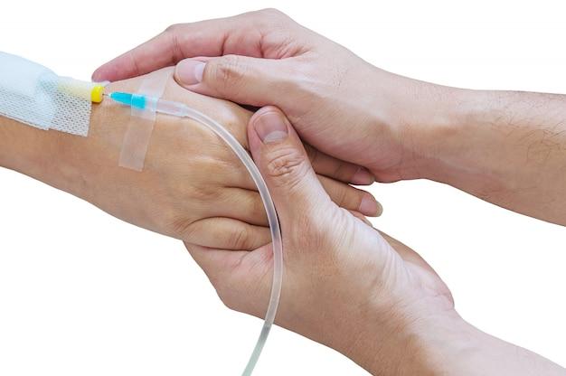 Мужчина держит женщину, пациента, руку с трубкой инъекции медицины на кровати в больнице