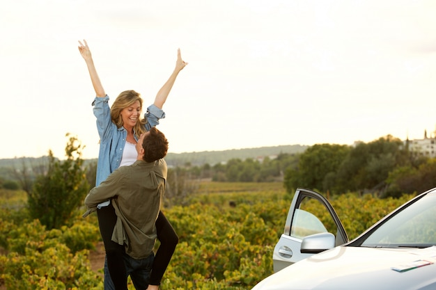 Man holding woman standing outside of car by field