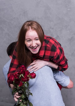 Man holding woman with roses on shoulder