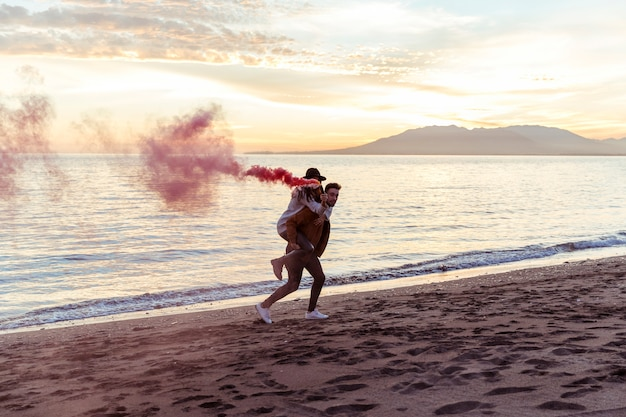 Man holding woman with smoke bomb on back on sea shore