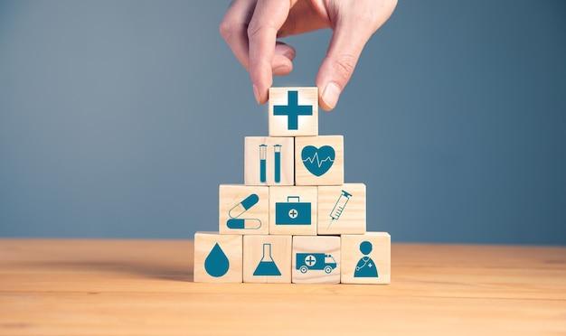 ヘルスケア医療のシンボルと木製のブロックを保持している男