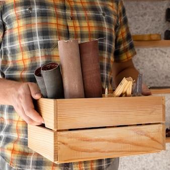 Uomo che tiene una scatola di legno con strumenti