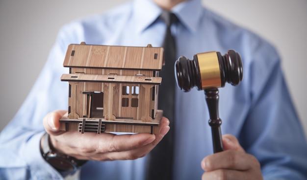 Мужчина держит деревянный дом и судья молотком.